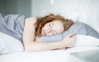Rothaariges-Mädchen-schläft-im-Bett